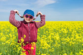 Girl in yellow field of rape — Stock Photo