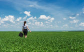 Girl with a briefcase walking on grass — Stock Photo