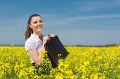 Girl with a briefcase on yellow flower field — Stock Photo