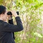 Woman using binoculars — Stock Photo #13373452