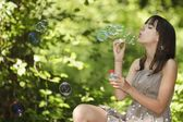 Girl blowing bubbles — Stock Photo