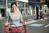 Woman and shopping cart — Stock Photo