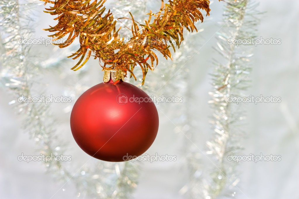 Red glass christmas ball hanging on a golden garland — Stock Photo #13371763