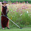 Housekeeper in flower bed — Stock Photo