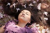 Mulher deitada em flores — Foto Stock