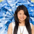 Beautiful young Thai girl under a blue sunshade — Stock Photo
