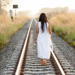 Young woman walking down a railway track — Stock Photo