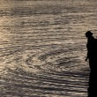 Father and son in the sea silhouetted at sunset — Stock Photo