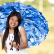 Beautiful young Thai girl under a blue sunshade — Stock Photo #44213571