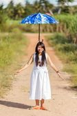 Young Thai girl balancing an umbrella on her head — Stock Photo