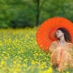 Beautiful elegant woman with an orange parasol — Stock Photo #49957871