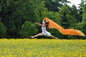 Agile woman leaping in the air trailing a scarf — Stockfoto