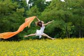 Agile woman leaping in the air trailing a scarf — Photo