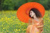 Beautiful elegant woman with an orange umbrella — Stock Photo