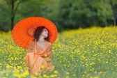 Beautiful elegant woman with an orange umbrella — Stock Photo