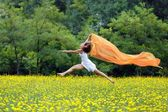 Agile woman leaping in the air trailing a scarf — Stok fotoğraf