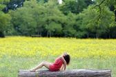Beautiful young woman relaxing on a log — Stock Photo