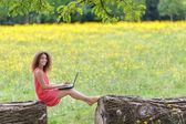 Young woman using laptop in nature — Stock Photo