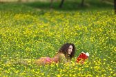 Cute young woman with curly hair lying reading — Stock Photo