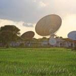 Satellite communication dish against flare light — Stock Photo