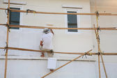 Worker on wooden scaffold painting house — Stock Photo