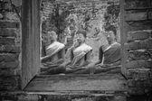 Meditating ancient buddha statues through window frame — Stock Photo