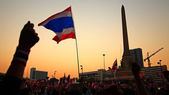 Thai flag and hands at Victory monument — Stock Photo