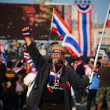 Stock Photo: Old protester with dress decorations raises Thai flag