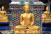 Three golden Buddha statues at Thai temple — Stock Photo