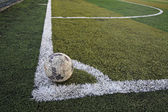 Old ball in new soccer field at corner  — Stock Photo