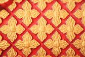 Patrón oro de flores en la pared roja — Foto de Stock