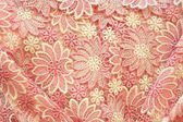 Texturd achtergrond van roze bloemen textiel — Stockfoto