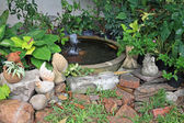 Chicken and pig statues at earthenware Fountain in garden — Stock fotografie
