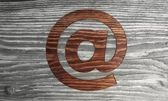 Wooden e mail symbol in a wooden background — Stock Photo