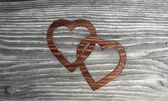 Cute two hearts symbol in a wooden background — Stock Photo