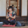 Wompraying in Buddhist temple — Stockfoto #16860719