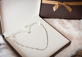 Valentines day gift - White gold necklace in a shape of heart — Stock Photo