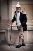 Old man with a funny hat and a walking stick — Stock Photo