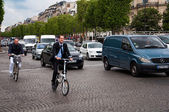 Business man on a bicycle at Champs Elysees street — Stock Photo
