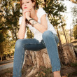 Beutiful redhead girl in a white t-shirt and jeans sitting on a tree stump — Foto de Stock