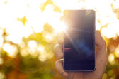 Man's hand holding smart phone against blurred nature background — Photo