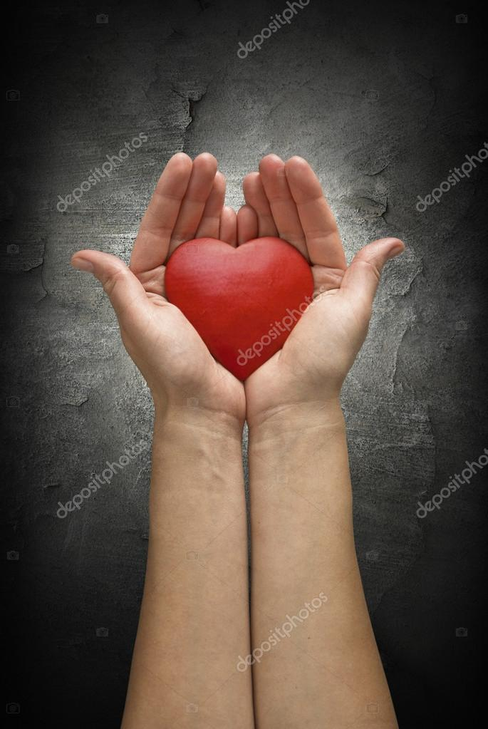 Woman hands holding heart over a dark concrete wall. Like a symbol of hope, love or peace. — Stock Photo #19634737