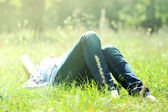 A girl lies on a grass — Stock Photo