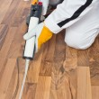 Appling silicone sealant in spaces of old wooden floor — Stock Photo