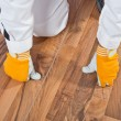 Worker analyzing wooden floor for cracks - Stock Photo