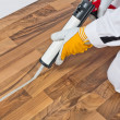 Worker applies silicone sealant spaces of old wooden floor — Stock Photo