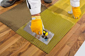 Applies tile adhesive on wooden floor with reinforce fiber mesh — Stock Photo
