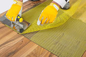 Applying tile adhesive with reinforcement mesh on wooden floor — Stock Photo