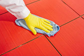 Hand with yellow gloves and blue towel clean red tiles grout — Stock Photo