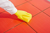 Hand with yellow gloves and yellow sponge clean red tiles — Stock Photo
